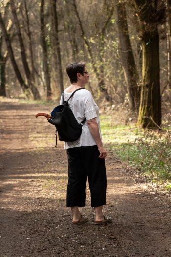 Tatjana Mücher auf einem Waldweg, schaut nach rechts, einen schwarzen Rucksack auf dem Rücken, ein brauner Sägegriff aus Holz schaut heraus. Es ist Sommer, sie trägt eine schwarze weitere Leinenhose, ein weißes, weites T-Shirt fällt locker darüber. Silberfarbene Sandalen an den Füßen. Die Sonne wirft lange Schatten, ein wunderbares Lichtspiel.